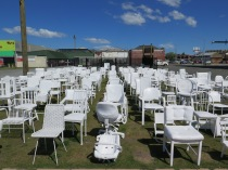 """185 square meters of grass depicting new growth, regeneration. 185 white chairs, all painted twice by hand as an act of remembrance. This installation is temporary - as is life."" - Pete Majendie"
